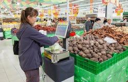 Jeune femme pesant des légumes sur les échelles électroniques Photos stock