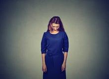 Jeune femme peu sûre timide triste se tenant regardante vers le bas photos libres de droits
