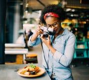 Jeune femme photographiant sa nourriture sur un compteur de café photographie stock libre de droits