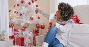 Jeune femme photographiant son arbre de Noël Photos stock