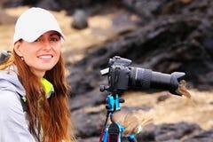 Jeune femme photographiant sur Santiago Island avec le FLYCATCHER de Galapagos sur son pare-soleil Photo stock