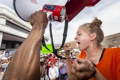 Jeune femme pleurant et hurlant dans le mégaphone aux RP de violence armée Photographie stock libre de droits