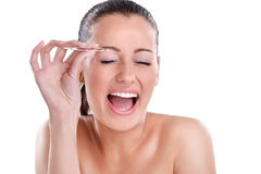 Jeune femme plumant ses sourcils avec des brucelles images stock