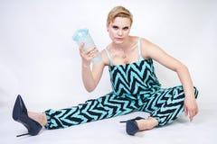 Jeune femme plus de charme de taille dans la salopette bleue noire avec le verre de l'eau sur le fond blanc dans le studio joli w photographie stock libre de droits