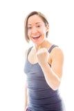 Jeune femme poinçonnant l'air et rire Photo libre de droits