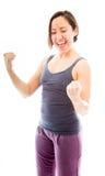 Jeune femme poinçonnant l'air et rire Photographie stock