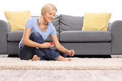 Jeune femme polissant ses ongles de pied Images stock