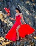 Jeune femme portant la longs robe et masque rouges Images stock