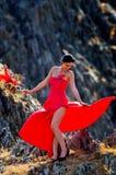 Jeune femme portant la longs robe et masque rouges image stock