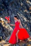 Jeune femme portant la longue robe rouge photos stock