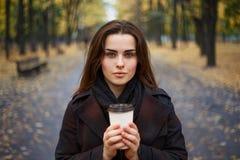 Jeune femme portant le manteau à carreaux élégant marchant pendant l'automne Image stock