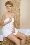Jeune femme portant une serviette dans la salle de bains Photographie stock libre de droits