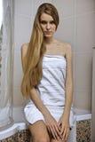 Jeune femme portant une serviette dans la salle de bains Photo stock