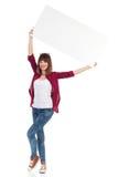Jeune femme posant avec l'affiche au-dessus de sa tête Images libres de droits