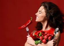 Jeune femme posant avec le peppe rouge frais de piments de radis de légumes image stock