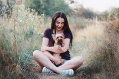Jeune femme posant avec son chien - terrier de Yorkshire sur la nature Image libre de droits