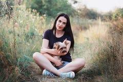 Jeune femme posant avec son chien - terrier de Yorkshire sur la nature Images libres de droits