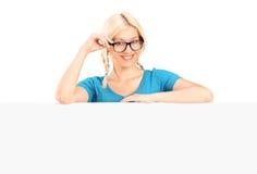 Jeune femme posant derrière un panneau blanc Image stock