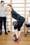 Jeune femme posant l'exercice avec la barre dans le gymnase Image libre de droits