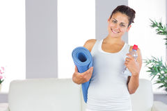 Jeune femme posant tenant un tapis d'exercice et une bouteille dans son salon images stock