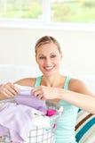Jeune femme positif faisant la blanchisserie photo stock