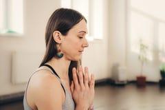 Jeune femme positive faisant le geste de main de namaste au studio image stock