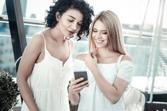 Jeune femme positive montrant son smartphone à son ami Images stock