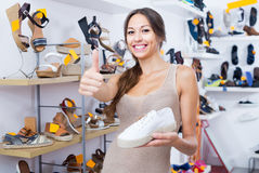 Jeune femme positive se tenant avec la chaussure choisie Image libre de droits