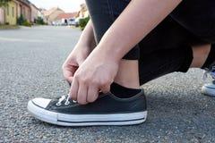 Jeune femme pour attacher des dentelles aux chaussures de sport Route goudronnée sur le chemin image stock