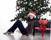 Jeune femme près d'arbre de nouvelle année avec le présent Image libre de droits
