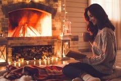 Jeune femme près de concept d'hiver de cheminée à la maison images stock