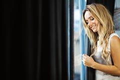 Jeune femme près de la fenêtre Image stock