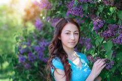 Jeune femme près du parc de buisson lilas au printemps photos stock
