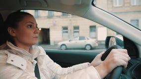 Jeune femme préoccupée dans la veste blanche conduisant la rue de ville de cuvette de voiture clips vidéos