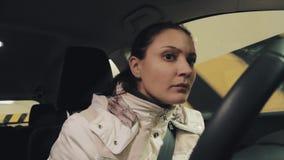 Jeune femme préoccupée dans la veste blanche conduisant le stationnement souterrain de cuvette de voiture banque de vidéos