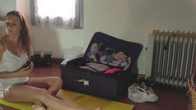 Jeune femme préparant des bagages banque de vidéos