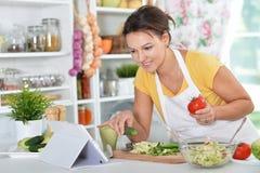 Jeune femme préparant le dîner sur la cuisine image libre de droits