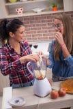 Jeune femme préparant le jus de detox du mélangeur Photographie stock libre de droits