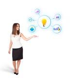 Jeune femme présent l'ampoule avec les graphiques et le diagr colorés Photographie stock libre de droits