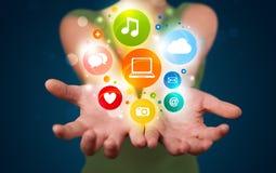 Jeune femme présent les icônes et les symboles colorés de technologie Image libre de droits