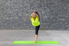 Jeune femme pratiquant la pose de yoga de Vrksasana images stock