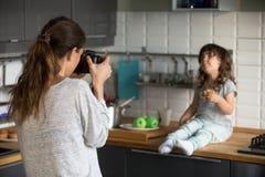 Jeune femme prenant à photo la petite fille mignonne dans la cuisine photo libre de droits