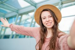 Jeune femme prenant à selfie un embarquement de attente de salon d'aéroport dans l'aéroport international Photos libres de droits