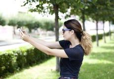 Jeune femme prenant des photos à votre téléphone Photo stock