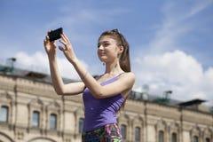 Jeune femme prenant des photos à votre téléphone Photo libre de droits