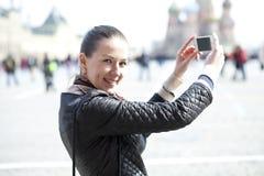 Jeune femme prenant des photos à votre téléphone Photos stock