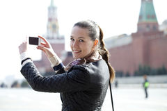 Jeune femme prenant des photos à votre téléphone Image libre de droits