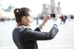 Jeune femme prenant des photos à votre téléphone Images libres de droits