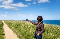 Jeune femme prenant des photos avec son téléphone portable Image stock