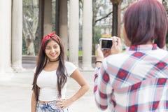 Jeune femme prenant des photos de ses amis en parc Photo libre de droits